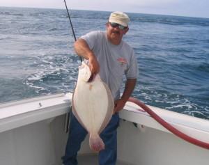 Carl Scuderi hefts a 10-plus doormat fluke he brought to net aboard the Fish Hawk at Nantucket.